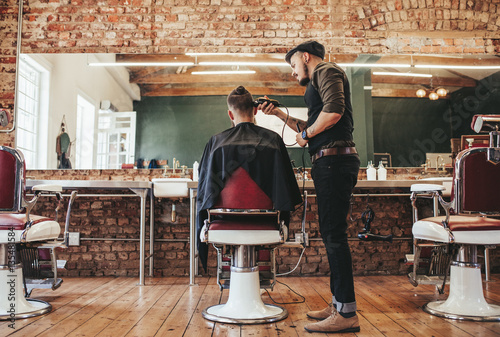 Hairstylist serving client at barber shop Poster