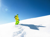 Man with snowboard staying in snow at sky background