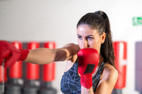 Poster Beautiful girl exercising with kick box training. Fitness and he