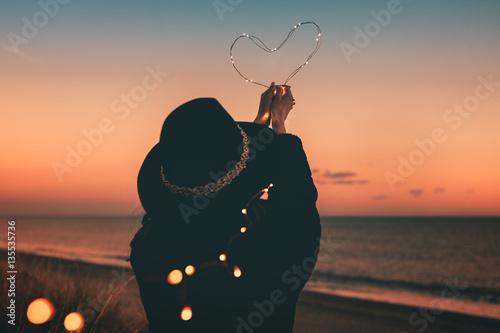Cuore luminoso tenuto in mano da una ragazza vestita di nera sulla spiaggia al tramonto. San Valentino Concetto.