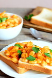 Open sandwiches with baked beans on a plate. Baked white beans in a bowl, bread slices, spoon on vintage wooden background. Vegetarian food for better health. Vertical photo