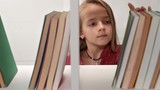 Little girl browsing the books on a bookshelf