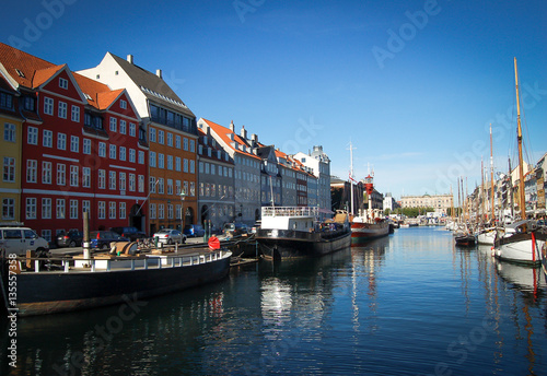 Poster copenhagen colored buildings on its river on a blue sky background