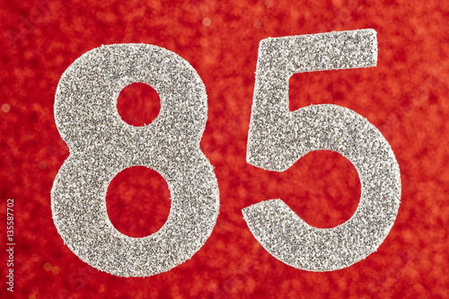 Poster Number eighty-five silver color over a red background. Anniversa