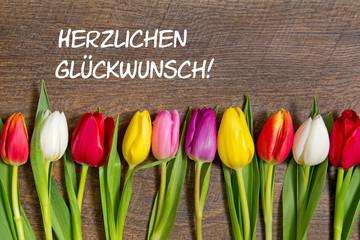 Tulpen auf Holzhintergrund: Herzlichen Glückwunsch