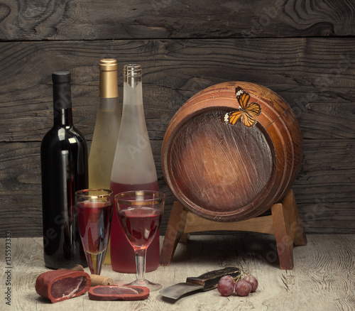 bottle of wine and wooden barrel for wine on a wooden table, still life, wine tavern