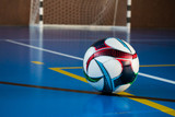 Soccer ball on the floor in the gym against the gate