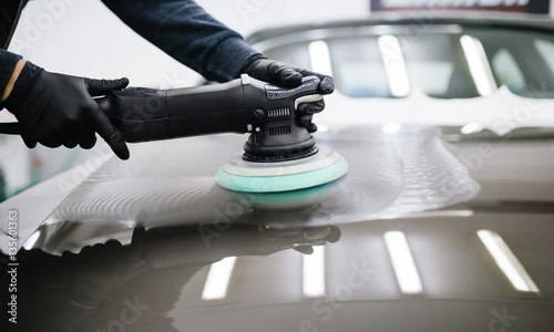 Car detailing - Hands with orbital polisher in auto repair shop. - 135601363