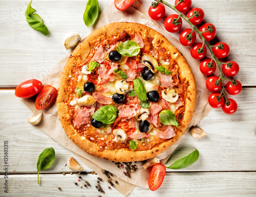 Pizza with ingredients served on wood