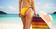 Medium shot of a young white girl standing next to her lounge chair in her yellow bikini