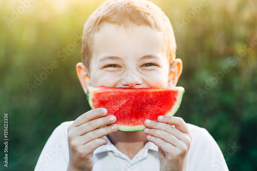 Poster Young caucasian boy a white shirt smiles with his watermelon