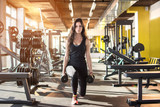 Young sporty woman doing exercises with weights in gym. - 135625386