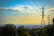 Sunset in the mountains over power lines with downtown Los Angeles skyline ithe the background.