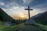 Wooden cross and colorful sunrise in a forested valley in the mountains of Switzerland