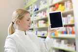 Young female pharmacist holding tablet with empty screen