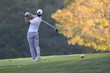 A muscular golfer tees off with his driver on an autumn day in New England with the Vermont foliage as bright as can be