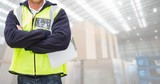 Worker standing with arms crossed in warehouse