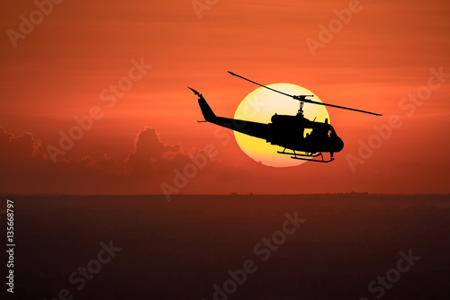 Poster Flying helicopter silhouettes on sunset background