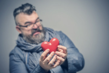 Adult bearded man in a blue jacket and scarf with disgust holding red heart. Toned