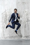 Jumping for joy man in blue suit