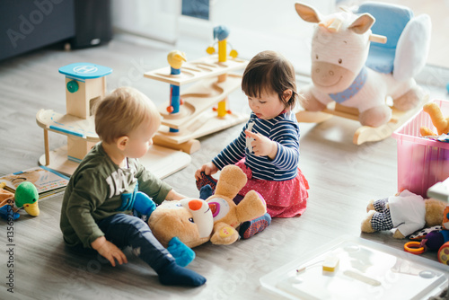 Fototapeta little girl and boy playing with toys by the home