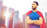man in red superhero cape over city skyscrapers