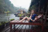 image of happy young woman at beach house on the River Kwai in Thailand