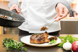 chef decorating roasted meat with mushroom sauce and herbs