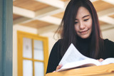 Beautiful Asian girl reading book in the house with smiley face