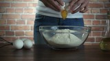 Woman crack egg in glass bowl with flour, slow motion hd video