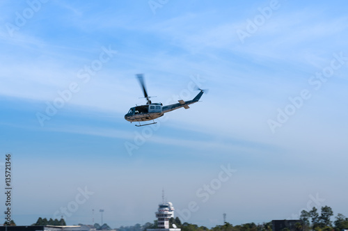 Poster Flying helicopter on blue sky background - bottom view