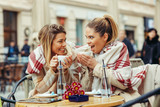 Two young women in a cafe have fun and gossiping - 135734925