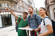 Young happy tourists sightseeing in city
