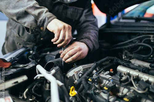 Auto mechanic repairing car. Selective focus. - 135737520