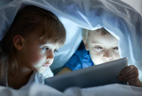 Fototapety Cute little children lying under blanket with tablet computer