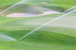 Sprinklers watering system working in green golf course.