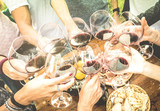 Friends hands toasting red wine glass and having fun outdoors cheering with winetasting - Young people enjoying harvest time together at farmhouse vineyard countryside - Youth and friendship concept - 135779160