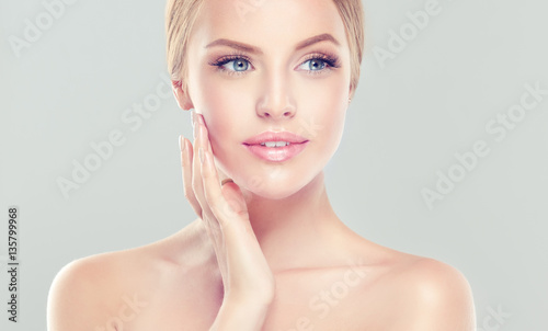 Leinwanddruck Bild Beautiful Young Woman with clean fresh skin . Facial treatment . Cosmetology , beauty and spa .