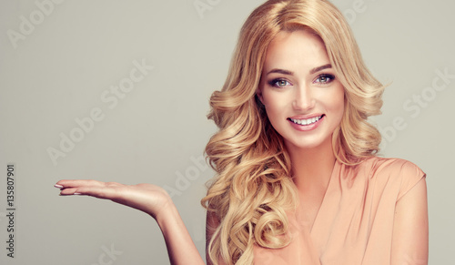 Blonde woman with curly hair shows your product . .Beautiful girl with beautiful smile pointing to the side . Presenting your product. Expressive facial expressions