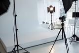 Photo studio with tripod, lighting equipment and digital camera - 135818359