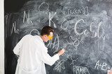 Chemist write a chemical formula on blackboard. Chemistry lesson. Study chemistry. Scientist at chemical laboratory. Crazy professor in yellow glasses.
