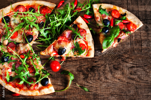 Hot pizza slice with Pepperoni, melting cheese on a rustic woode Poster