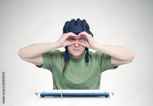 Man in a tank helmet looks through fingers like binoculars Poster