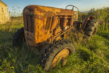 Abandoned red old rusty tractor in a field