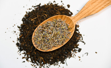 loose dried lavender flower seeds for cosmetic use or tea infusion ,decorative serving on a wooden spoon on black tea on white background
