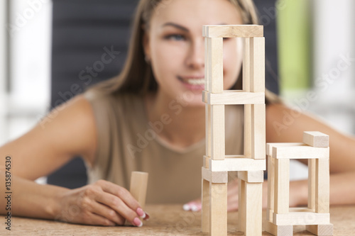 Smiling girl is playing with wood bricks Poster