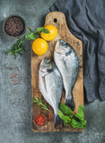 Fresh uncooked sea bream or dorado fish with lemon, herbs and spices in bowls on rustic wooden board over grey concrete background, top view. Healthy, dieting, clean eating concept