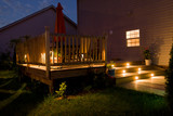 Wooden deck and patio of family home at night. - 135879551