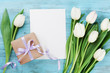 Spring tulip flowers, gift box and paper card on turquoise vintage table from above in flat lay style. Greeting for Womens or Mothers Day.