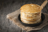 Stack of pancakes on a cast-iron frying pan,on wooden background. Style rustic.